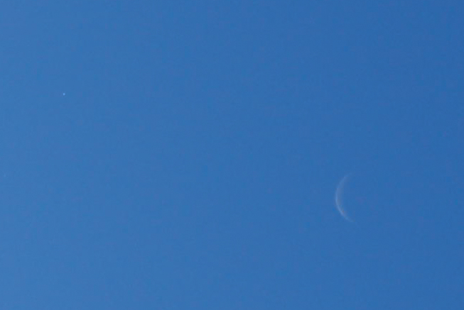 The crescent Moon and the planet Venus (at upper left) in near local noon on October 8, 2015.