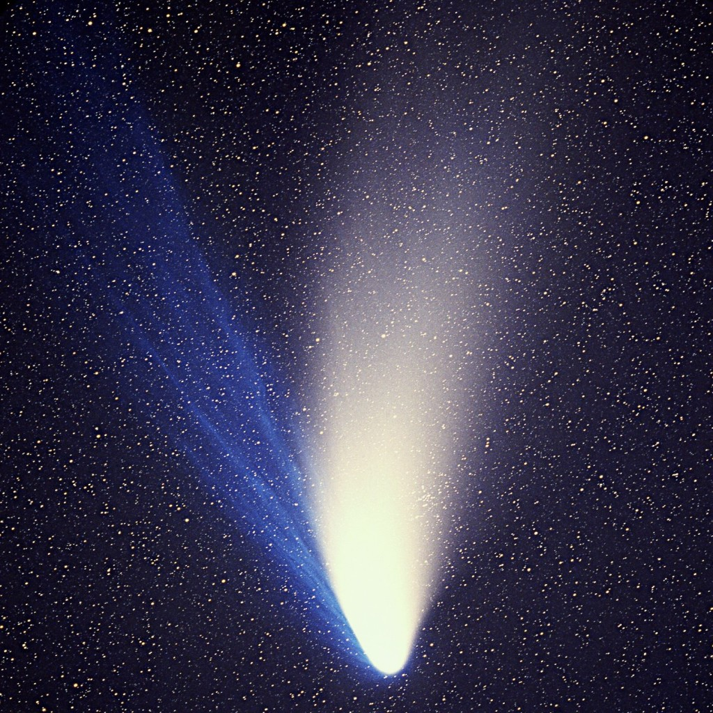 Close-up of Comet Hale-Bopp showing the blue ion tail and yellow-white dust tail.